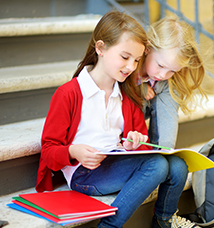 Students sitting on steps looking at a folder together