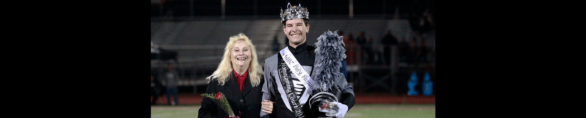 Homecoming king and a woman pose together outside