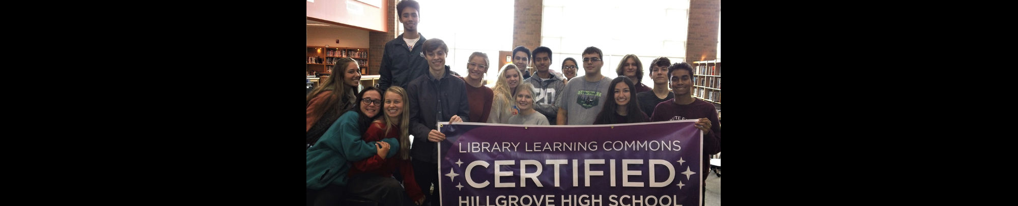 students with a banner that Library Learning Commons Hillgrove high School