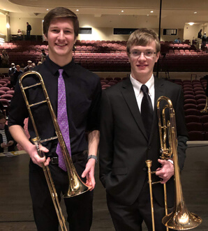 Two students holding trumpets