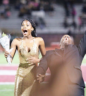 Homecoming couple on football field looking surprised