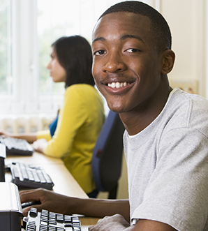 Student sitting at a computer terminal with woman in background