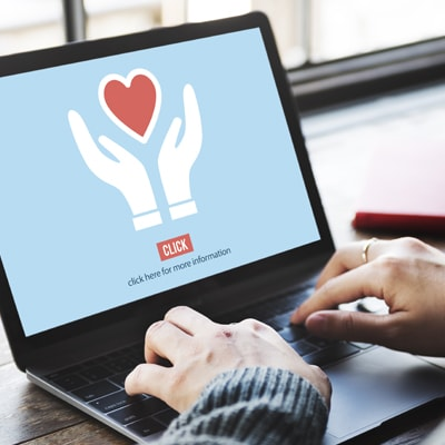 computer with hands and heart on screen