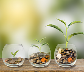 Investment concept with three plants in glass containers