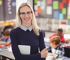 Happy female teacher standing in front of classroom