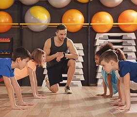 Children being coached in gymnasium