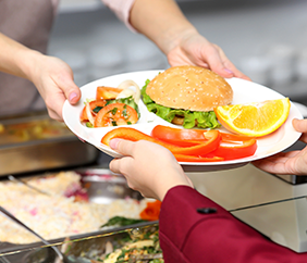Cafeteria worker handing a student a healthy meal