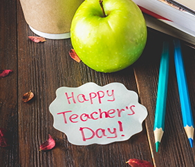 Happy Teachers Day hand-written note on wood table along with an apple
