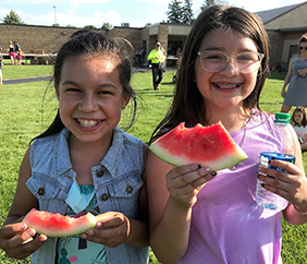Two happy girls eating watermelon during an outdoor school activity