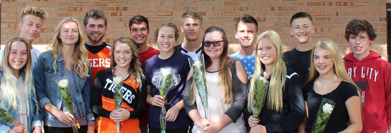 students holding flowers,smiling