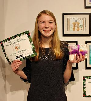 student smiling holding her award