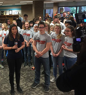 Students being interviewed with news anchor and videographer