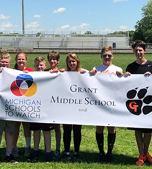 Students on a field holding Michigan Schools To Watch Sign with Grant Middle School 2018 and the school logo
