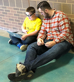 Student and teacher sit on floor looking at laptop together
