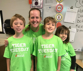 Teacher and three students wearing green Tiger Tuesday t-shirts