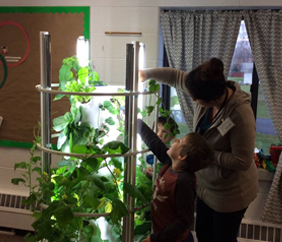 Students looking at a plant with a teacher