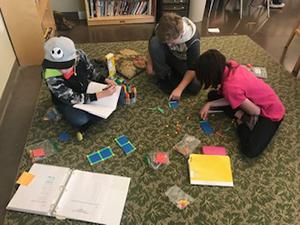Students practice math skills using algebra tiles