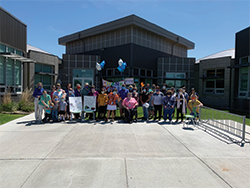 Students, staff and teachers pose together outside with teacher appreciation signs