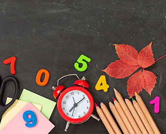 Colored pencils, numbers, clock on a black background