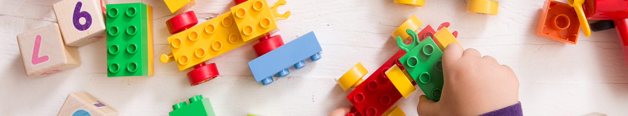 Child's hands play with lego blocks and wood blocks on a wood table