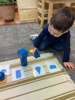 Preschool boy playing with geometric solids