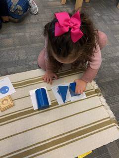 Preschool girl playing with geometric solids