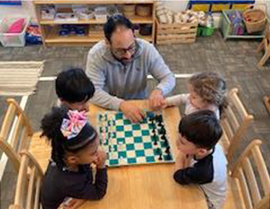 One teacher teaching four students how to play chess.