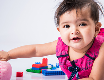 Infant plays with toy blocks