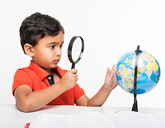 Child holds a magnifying glass in front of a globe