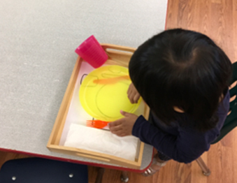 Toddler sitting at a table playing with a plate and fork
