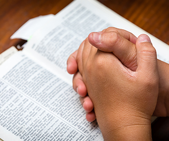 Child holds his hands in prayer above a scripture book