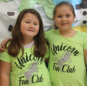 Two smiling female students pose together wearing shirts that say Unicorn Fan Club