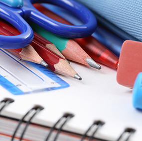 Pencils, pens, erasers, scissors and a ruler on top of a notebook