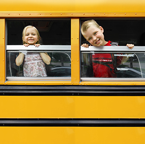Two students stick their heads outside of a school bus window