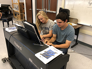 Two students playing the piano together in the music appreciation class