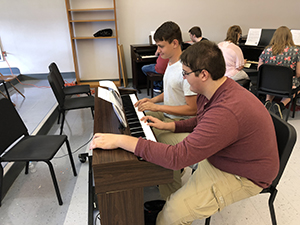 Male students practicing the piano in the music appreciation class