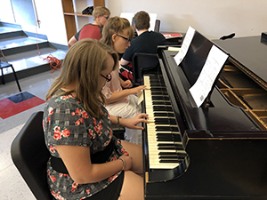 Female students playing the piano in the music appreciation class