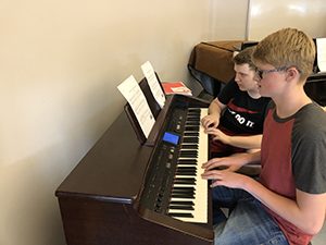 Students practicing the piano in the music appreciation class