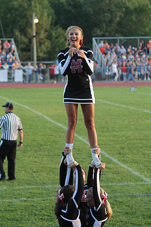 Cheerleaders cheer on a field and football player stands on a field