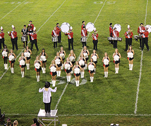 Band members and cheerleaders perform on a field