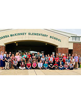 Students stand in front of Super Reader wall