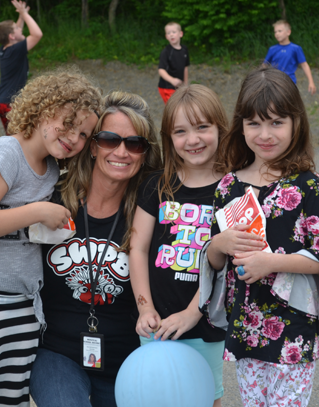 Teacher smiling with three girl students