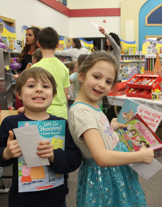 Two students holding books at a book fair