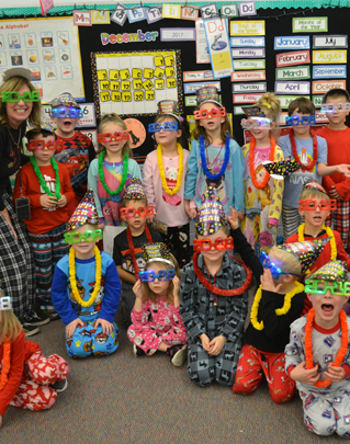 Students in pajamas with silly glasses, hats, and leis