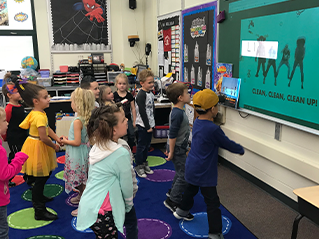 Students dance along to a video with the words clean, clean, clean up on a screen