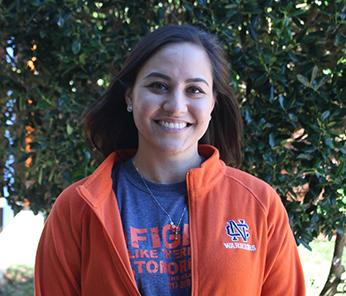 Smiling female student wearing orange North Cobb jacket