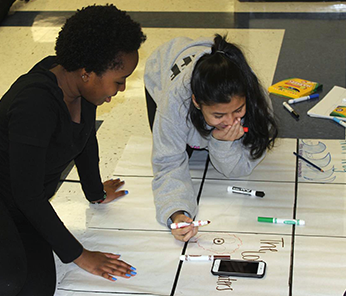 Two female students working on a project on the classroom floor