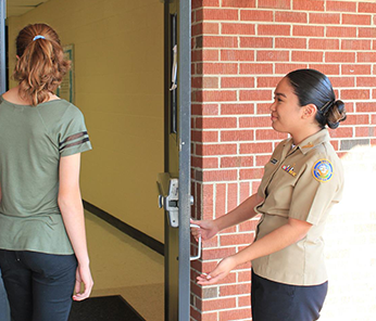 JROTC student opening the door for another student