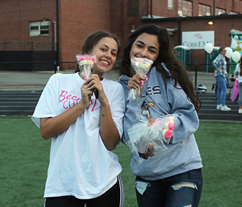 Two happy female students outside holding cake pops
