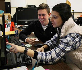 Two students working in front of a computer